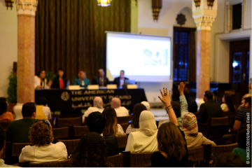 A table of panelists face an audience, several of whom are raising hands