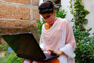 A woman in a mask sits typing on a laptop outside