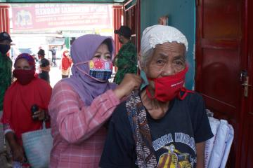 A woman wearing a mask helps an older woman to tie on her mask.