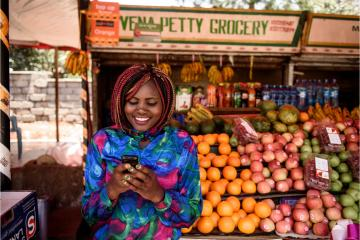 Woman uses mobile phone to make cash transfer in front of fruit stand
