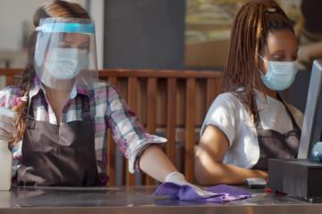 Two female cashiers wearing face masks clean a counter.