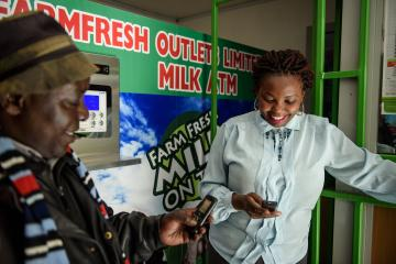 A man and woman use their phones for a mobile money transfer