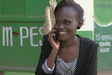 A smiling women speaks on a cell phone in front of an Mpesa stand.