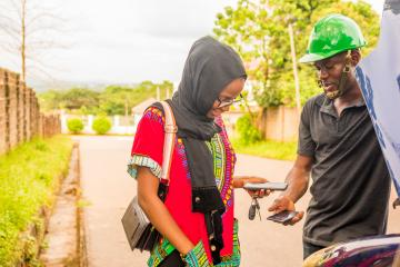 A woman pays mechanic through a mobile phone transfer