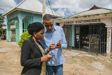 A man and woman look at their mobile phones