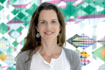 Kelly Bidwell stands in front of a colorful pattern backdrop