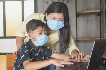 Mother helping child study online.