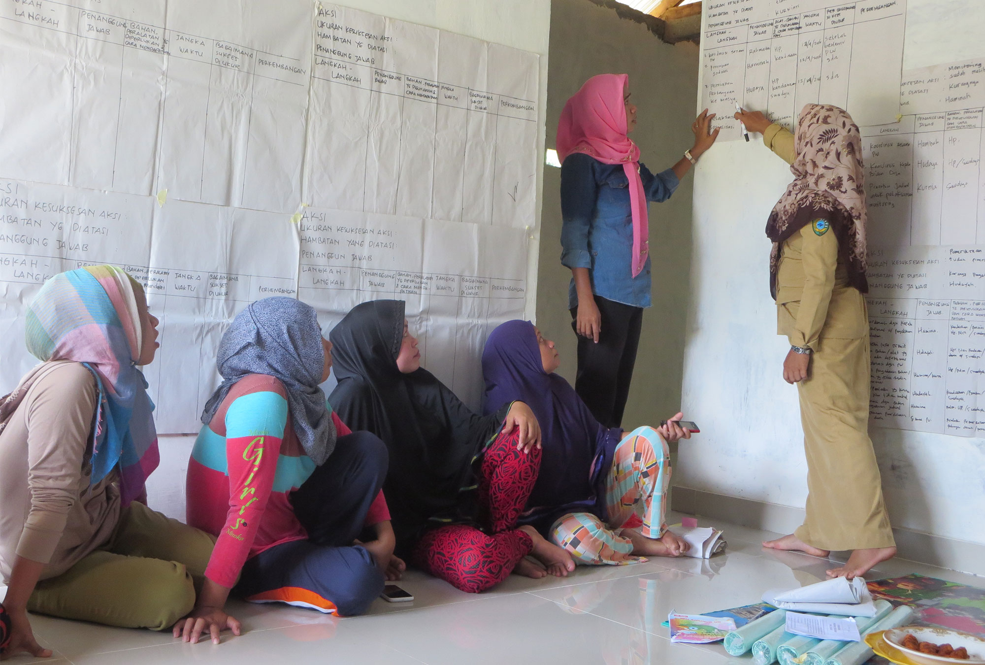 Group of women in room with walls covered in paper which they are taking notes on and discussing
