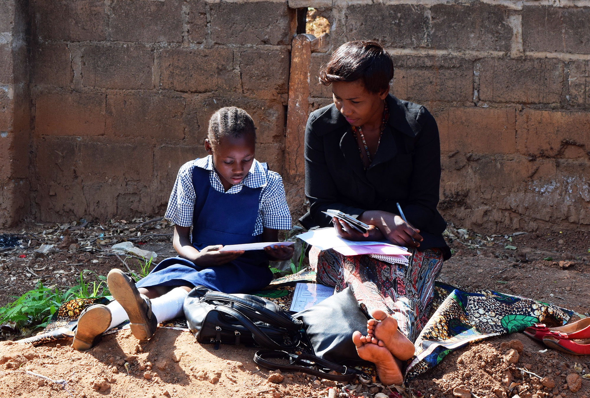 Woman sits reading a book with a child in school uniform