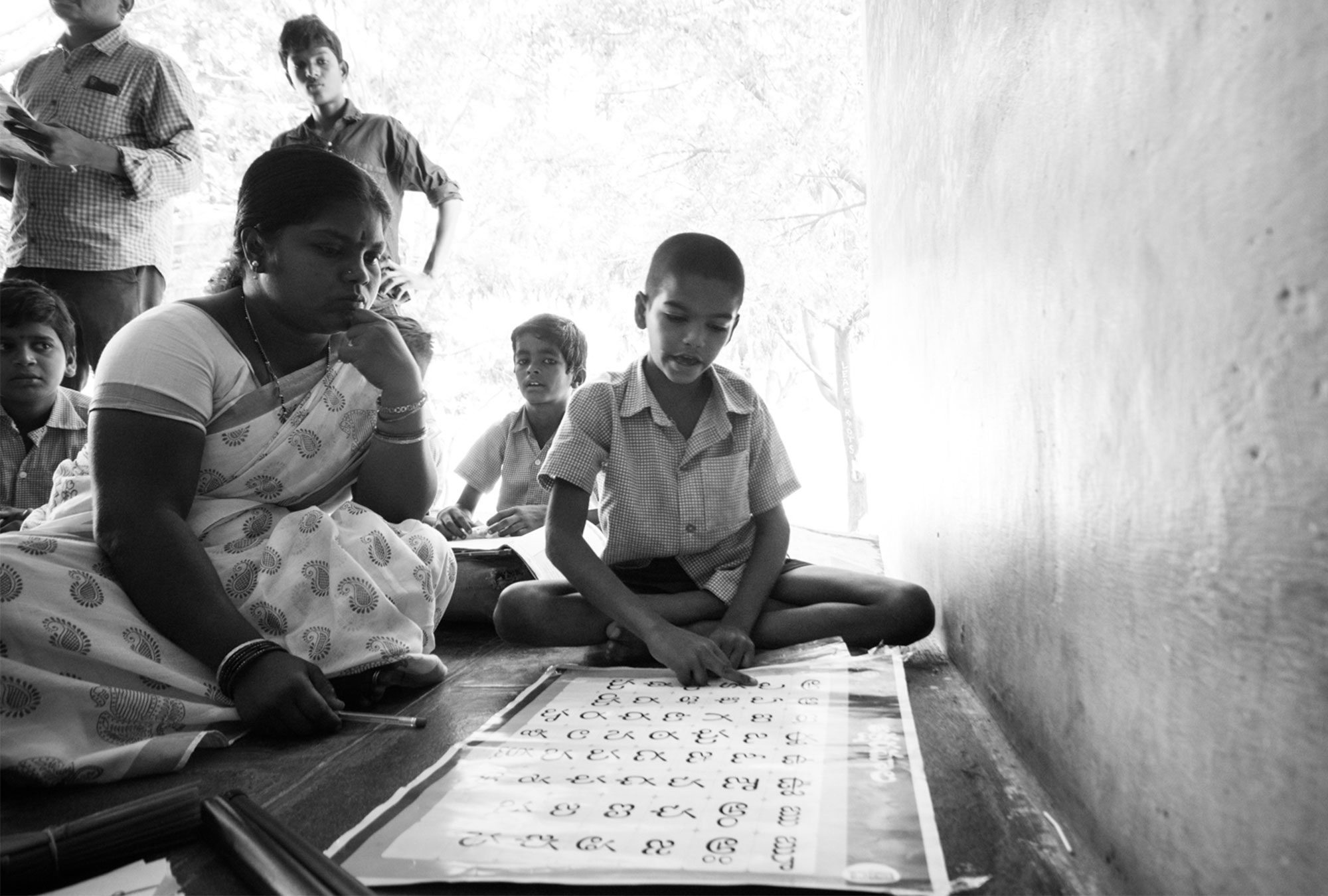 A teacher assists student in reading the alphabet